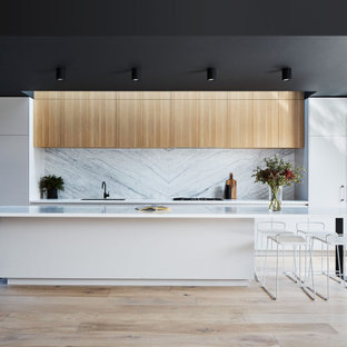 Inspiration for a contemporary galley kitchen in Melbourne with an undermount sink, flat-panel cabinets, light wood cabinets, white splashback, stone slab splashback, panelled appliances, light hardwood floors, with island, beige floor and white benchtop.