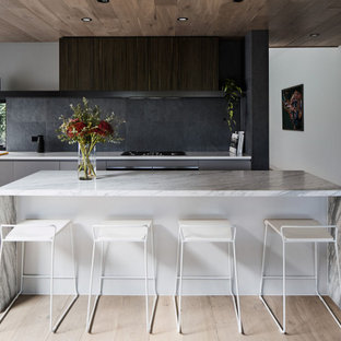 Contemporary galley kitchen in Melbourne with flat-panel cabinets, grey cabinets, black splashback, light hardwood floors, with island, beige floor and white benchtop.