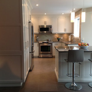 Example of a trendy u-shaped enclosed kitchen design in Montreal with a single-bowl sink, shaker cabinets, white cabinets, quartz countertops, beige backsplash, stone tile backsplash and stainless steel appliances