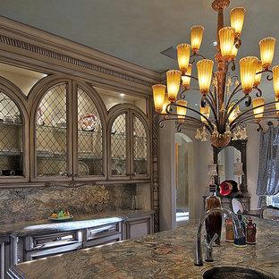 Idée de décoration pour une grand cuisine américaine méditerranéenne en U avec un évier 3 bacs, un placard avec porte à panneau encastré, des portes de placard beiges, un plan de travail en granite, une crédence grise, une crédence en dalle de pierre, un électroménager en acier inoxydable, un sol en carrelage de céramique, un îlot central et un sol marron.