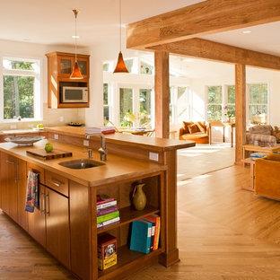 ボルチモアの中サイズのトラディショナルスタイルのおしゃれなキッチン (フラットパネル扉のキャビネット、中間色木目調キャビネット、木材カウンター、アンダーカウンターシンク、ベージュキッチンパネル、石タイルのキッチンパネル、シルバーの調理設備、無垢フローリング) の写真