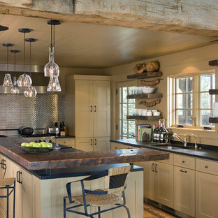 Inspiration for a mid-sized country l-shaped eat-in kitchen in Other with an undermount sink, flat-panel cabinets, beige cabinets, wood benchtops, metallic splashback, metal splashback, stainless steel appliances, with island and dark hardwood floors.