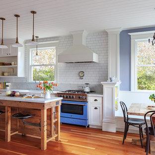 Einzeilige Klassische Wohnküche mit Landhausspüle, offenen Schränken, weißen Schränken, Marmor-Arbeitsplatte, Küchenrückwand in Weiß, Rückwand aus Metrofliesen, bunten Elektrogeräten, braunem Holzboden, Kücheninsel und grauer Arbeitsplatte in San Francisco