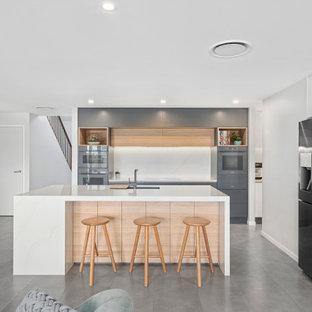 Стильный дизайн: угловая кухня-гостиная среднего размера в стиле модернизм с врезной раковиной, плоскими фасадами, серыми фасадами, столешницей из кварцевого композита, белым фартуком, фартуком из каменной плиты, цветной техникой, полом из керамогранита, островом, серым полом и белой столешницей - последний тренд