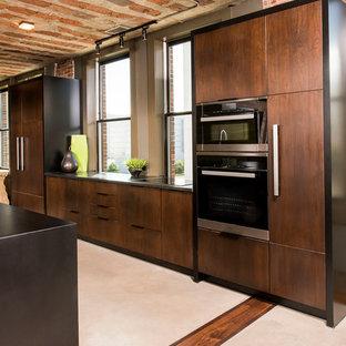 Zweizeilige, Große Industrial Küche mit Vorratsschrank, Unterbauwaschbecken, flächenbündigen Schrankfronten, dunklen Holzschränken, Granit-Arbeitsplatte, Elektrogeräten mit Frontblende, Betonboden, zwei Kücheninseln und beigem Boden in Raleigh
