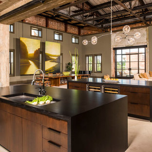 Inspiration for a large industrial open plan kitchen in Raleigh with an undermount sink, flat-panel cabinets, dark wood cabinets, granite benchtops, concrete floors, multiple islands and beige floor.