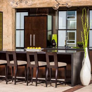 Große Industrial Küche mit flächenbündigen Schrankfronten, dunklen Holzschränken, Granit-Arbeitsplatte, Elektrogeräten mit Frontblende, Betonboden, beigem Boden, Rückwand-Fenster und zwei Kücheninseln in Raleigh