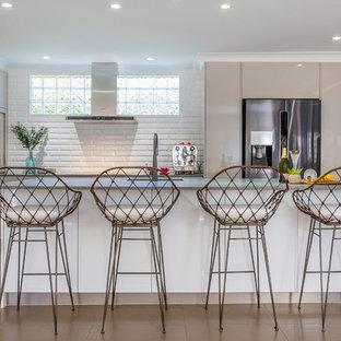 Design ideas for a large beach style l-shaped open plan kitchen in Brisbane with beige cabinets, white splashback, subway tile splashback, stainless steel appliances, with island, beige floor, grey benchtop, an undermount sink, quartz benchtops and porcelain floors.
