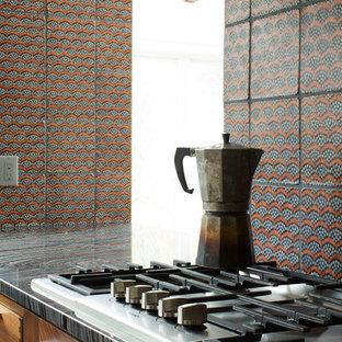 ニューヨークの中サイズのモダンスタイルのおしゃれなキッチン (アンダーカウンターシンク、フラットパネル扉のキャビネット、中間色木目調キャビネット、マルチカラーのキッチンパネル、テラコッタタイルのキッチンパネル、黒い調理設備、淡色無垢フローリング、マルチカラーのキッチンカウンター、オニキスカウンター) の写真