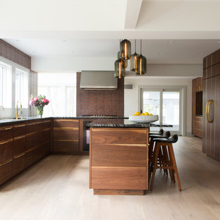 Contemporary kitchen inspiration - Trendy u-shaped light wood floor and beige floor kitchen photo in New York with an undermount sink, flat-panel cabinets, dark wood cabinets, red backsplash, paneled appliances, an island, black countertops and marble countertops