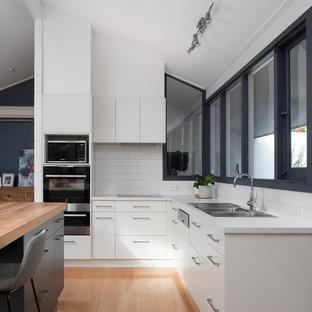 Design ideas for a contemporary l-shaped kitchen in Hobart with a drop-in sink, flat-panel cabinets, white cabinets, white splashback, stainless steel appliances, medium hardwood floors, with island, brown floor and white benchtop.