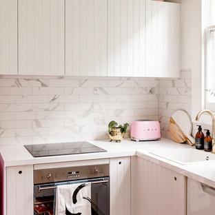 Idee per una piccola cucina a L bohémian chiusa con lavello da incasso, ante bianche, top in laminato, paraspruzzi bianco, paraspruzzi in marmo, elettrodomestici bianchi e nessuna isola