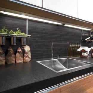 Ejemplo de cocina comedor de galera, contemporánea, de tamaño medio, con salpicadero negro, electrodomésticos de acero inoxidable y suelo de baldosas de porcelana