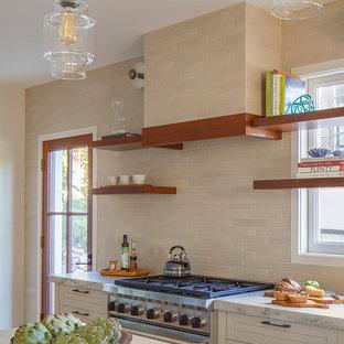 Идея дизайна: кухня в средиземноморском стиле с фасадами с декоративным кантом, столешницей из кварцита, бежевым фартуком, фартуком из керамической плитки, техникой из нержавеющей стали, бежевыми фасадами и островом