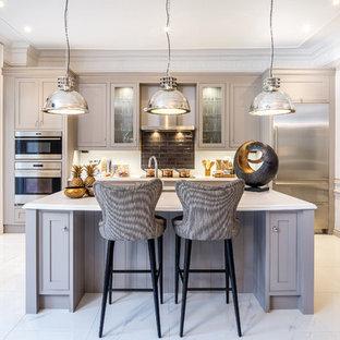 Cette image montre une cuisine traditionnelle avec un placard à porte vitrée, une crédence marron, une crédence en carrelage métro, un électroménager en acier inoxydable, un îlot central et des portes de placard grises.