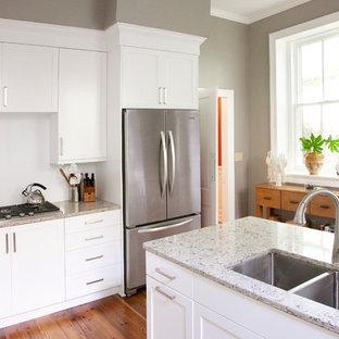 Exemple d'une cuisine chic avec un évier 2 bacs, des portes de placard blanches, un plan de travail en quartz modifié, une crédence blanche, une crédence en feuille de verre, un électroménager en acier inoxydable et un placard à porte shaker.