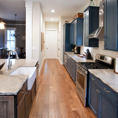 Elegant galley kitchen photo in Charleston with blue cabinets, concrete countertops, a farmhouse sink, shaker cabinets and stainless steel appliances
