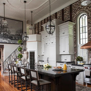 Large victorian galley kitchen in Charleston with recessed-panel cabinets, white cabinets, stainless steel appliances, medium hardwood floors and with island.