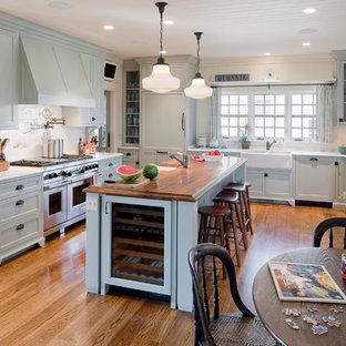 プロビデンスの大きいビーチスタイルのおしゃれなキッチン (エプロンフロントシンク、シェーカースタイル扉のキャビネット、グレーのキャビネット、白いキッチンパネル、パネルと同色の調理設備、木材カウンター、無垢フローリング) の写真