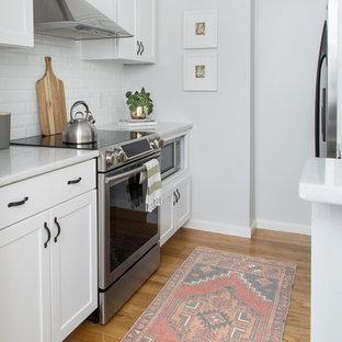 Modelo de cocina de galera, clásica renovada, pequeña, con armarios estilo shaker, puertas de armario blancas, salpicadero de azulejos tipo metro, electrodomésticos de acero inoxidable, suelo de madera en tonos medios y salpicadero blanco