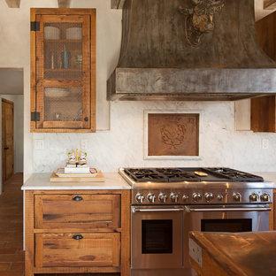 Ispirazione per una cucina country di medie dimensioni con lavello stile country, ante in stile shaker, ante con finitura invecchiata, top in marmo, paraspruzzi bianco, paraspruzzi in lastra di pietra, elettrodomestici da incasso, pavimento in terracotta, isola, pavimento rosso e top bianco