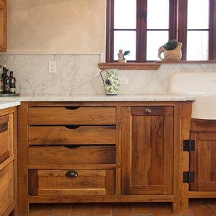 На фото: угловая кухня среднего размера в стиле кантри с раковиной в стиле кантри, мраморной столешницей, обеденным столом, фасадами в стиле шейкер, искусственно-состаренными фасадами, белым фартуком, фартуком из каменной плиты, техникой под мебельный фасад, полом из терракотовой плитки, островом, красным полом и белой столешницей с