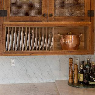 ナッシュビルの中サイズのカントリー風おしゃれなキッチン (エプロンフロントシンク、シェーカースタイル扉のキャビネット、ヴィンテージ仕上げキャビネット、大理石カウンター、白いキッチンパネル、石スラブのキッチンパネル、パネルと同色の調理設備、テラコッタタイルの床、赤い床、白いキッチンカウンター) の写真