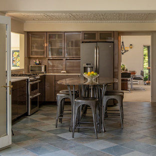 Transitional kitchen pictures - Kitchen - transitional u-shaped gray floor kitchen idea in Other with flat-panel cabinets, brown cabinets, brown backsplash, stainless steel appliances, an island and blue countertops