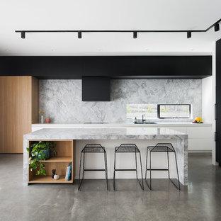 Nordische Küche in L-Form mit Doppelwaschbecken, flächenbündigen Schrankfronten, schwarzen Schränken, Küchenrückwand in Weiß, schwarzen Elektrogeräten, Betonboden, Kücheninsel, grauem Boden und weißer Arbeitsplatte in Melbourne