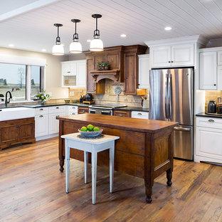 Große Landhausstil Küche in L-Form mit Landhausspüle, weißen Schränken, Granit-Arbeitsplatte, Rückwand aus Travertin, Küchengeräten aus Edelstahl, Kücheninsel, schwarzer Arbeitsplatte, profilierten Schrankfronten, Küchenrückwand in Beige und braunem Holzboden in Sonstige