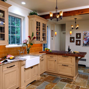 Large arts and crafts u-shaped eat-in kitchen in Charlotte with a farmhouse sink, beaded inset cabinets, brown cabinets, granite benchtops, stainless steel appliances, terra-cotta floors, no island, beige splashback, limestone splashback and grey floor.