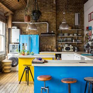 Stilmix Küche in U-Form mit flächenbündigen Schrankfronten, gelben Schränken, Rückwand aus Backstein, bunten Elektrogeräten, hellem Holzboden, zwei Kücheninseln, beigem Boden und beiger Arbeitsplatte in London