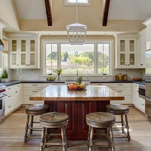 Foto på ett mellanstort lantligt flerfärgad kök, med en rustik diskho, skåp i shakerstil, vita skåp, träbänkskiva, vitt stänkskydd, stänkskydd i tunnelbanekakel, rostfria vitvaror, mellanmörkt trägolv, en köksö och brunt golv