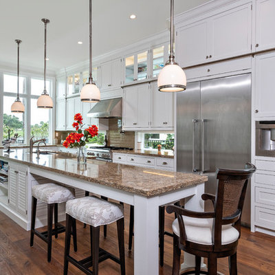 Island style l-shaped medium tone wood floor and brown floor kitchen photo in Miami with an undermount sink, shaker cabinets, white cabinets, brown backsplash, subway tile backsplash, stainless steel appliances, an island and brown countertops