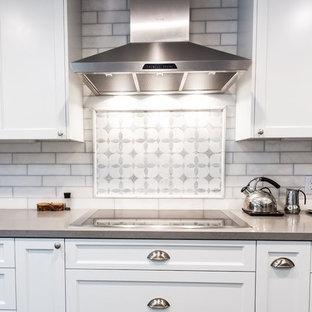Ispirazione per un'ampia cucina minimalista con lavello stile country, ante in stile shaker, ante bianche, top in granito, paraspruzzi bianco, paraspruzzi con piastrelle diamantate, elettrodomestici in acciaio inossidabile, pavimento con piastrelle in ceramica e isola
