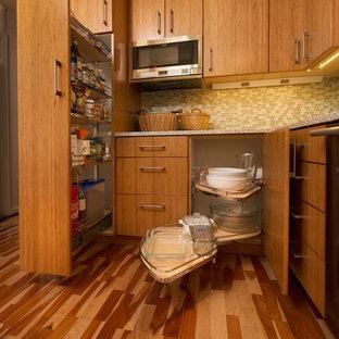 Imagen de cocina comedor en U, tradicional renovada, pequeña, con fregadero bajoencimera, armarios con paneles lisos, puertas de armario de madera oscura, encimera de vidrio reciclado, salpicadero gris, electrodomésticos de acero inoxidable, suelo de madera en tonos medios y península