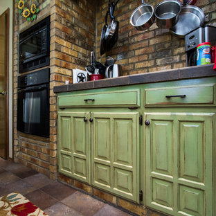 オースティンの中くらいのシャビーシック調のおしゃれなキッチン (レイズドパネル扉のキャビネット、緑のキャビネット、タイルカウンター、茶色いキッチンパネル、黒い調理設備、セラミックタイルの床、レンガのキッチンパネル) の写真
