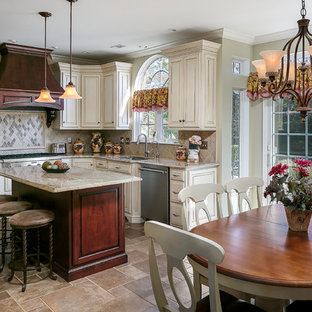 Traditional open concept kitchen appliance - Inspiration for a timeless l-shaped open concept kitchen remodel in Philadelphia with an undermount sink, raised-panel cabinets, white cabinets, beige backsplash, stainless steel appliances and an island