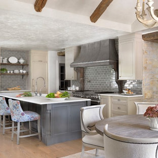 Inspiration for a traditional eat-in kitchen in St Louis with recessed-panel cabinets, beige cabinets, grey splashback, subway tile splashback, stainless steel appliances, medium hardwood floors, with island and white benchtop.