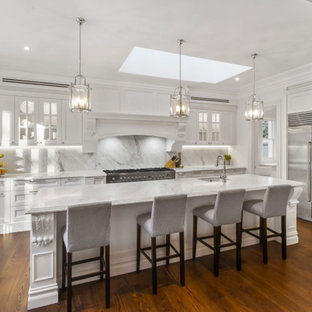 Design ideas for a traditional l-shaped kitchen in Sydney with an undermount sink, recessed-panel cabinets, white cabinets, white splashback, stainless steel appliances, dark hardwood floors, with island, brown floor and white benchtop.