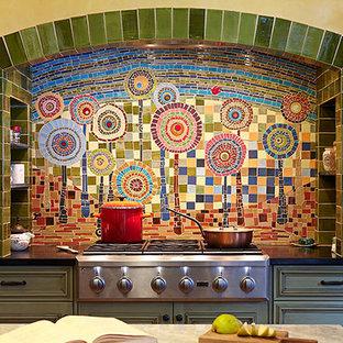 チャールストンの広いエクレクティックスタイルのおしゃれなキッチン (エプロンフロントシンク、レイズドパネル扉のキャビネット、緑のキャビネット、テラコッタタイルの床、オレンジの床) の写真