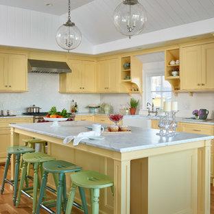 Modelo de cocina en L, costera, con fregadero sobremueble, puertas de armario amarillas, encimera de mármol, salpicadero blanco, electrodomésticos con paneles, suelo de madera clara, una isla, encimeras blancas y armarios con paneles empotrados