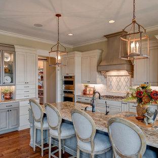 Inredning av ett klassiskt stort beige beige kök, med en rustik diskho, luckor med upphöjd panel, vita skåp, integrerade vitvaror, mellanmörkt trägolv, en köksö, brunt golv, granitbänkskiva, vitt stänkskydd och stänkskydd i marmor