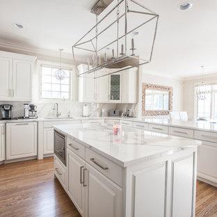 Exempel på ett stort klassiskt kök, med en undermonterad diskho, luckor med upphöjd panel, vita skåp, bänkskiva i kvarts, grått stänkskydd, stänkskydd i sten, integrerade vitvaror, mellanmörkt trägolv, en köksö och brunt golv