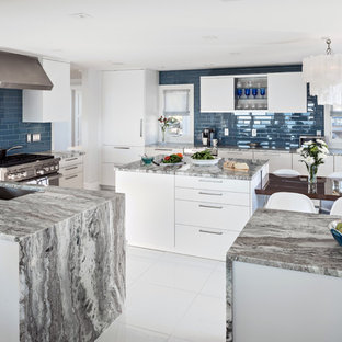 Inspiration for a large contemporary u-shaped open plan kitchen in Boston with a submerged sink, flat-panel cabinets, white cabinets, granite worktops, blue splashback, metro tiled splashback, stainless steel appliances, ceramic flooring, an island, white floors and multicoloured worktops.