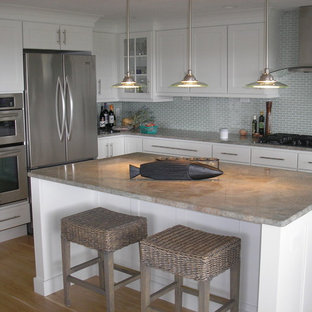 Example of a mid-sized trendy l-shaped light wood floor eat-in kitchen design in Boston with shaker cabinets, white cabinets, quartz countertops, blue backsplash, glass tile backsplash, stainless steel appliances and an island