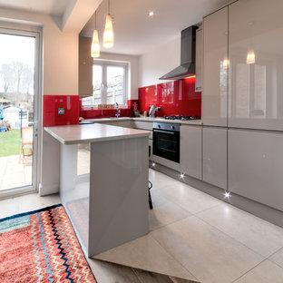 Zweizeilige, Mittelgroße Moderne Wohnküche mit flächenbündigen Schrankfronten, roten Schränken, Granit-Arbeitsplatte und Kücheninsel in London