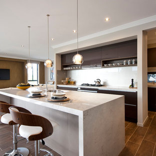 Contemporary galley open plan kitchen in Sydney with flat-panel cabinets, brown cabinets, white splashback, porcelain floors and with island.