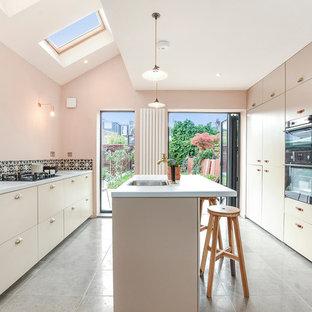 Esempio di una grande cucina design con lavello sottopiano, ante lisce, ante beige, paraspruzzi con piastrelle di cemento, elettrodomestici neri e penisola