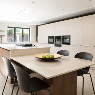 Large contemporary l-shaped kitchen/diner in London with an integrated sink, flat-panel cabinets, beige cabinets, quartz worktops, beige splashback, stone slab splashback, black appliances, porcelain flooring, an island, beige floors and beige worktops.